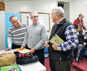 Brothers Hector, John and Santos review the weekly schedule at ComUnidad Juan Diego.